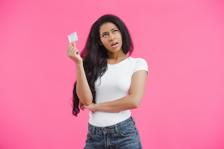 skeptical young african american woman holding condom isolated on pink background Stock Photo