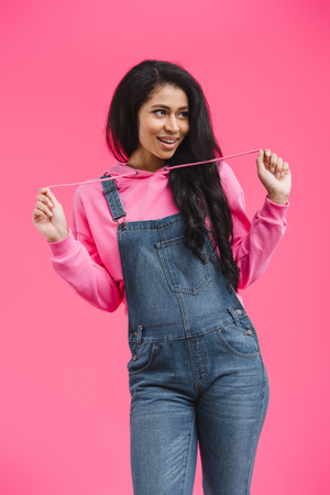 smiling african american woman tying hoodie laces and looking away isolated on pink background