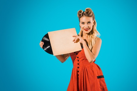 portrait of young pin up woman in stylish vintage dress with vinyl record on blue backdrop