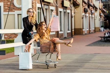 beautiful young women riding shopping cart during shopping together