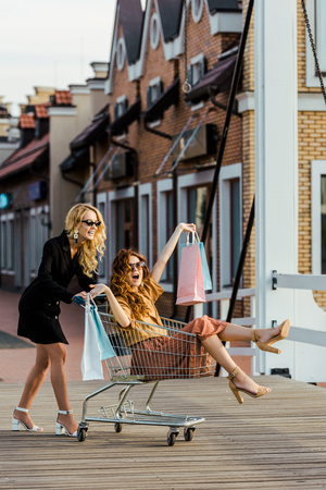 stylish young women riding shopping cart during shopping together