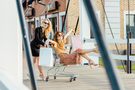 happy stylish young women riding shopping cart during shopping together