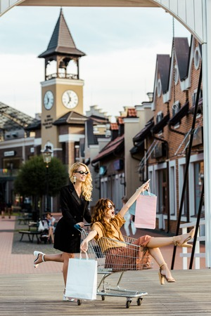 fashionable  young women riding shopping cart during shopping together