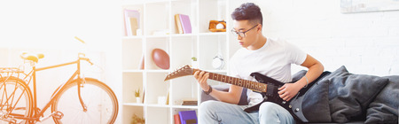 panoramic view of handsome left-handed asian man playing electric guitar on sofa at home Stock Photo