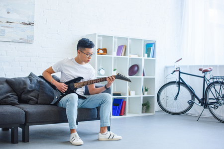 handsome asian man playing black electric guitar on sofa at home Stock Photo - 109989724