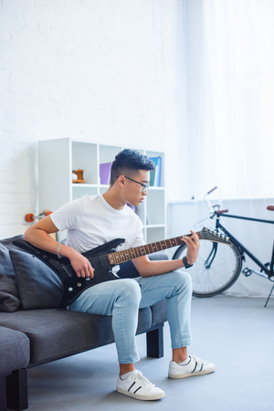handsome asian man playing F major chord on unplugged electric guitar at home Stock Photo - 110897283