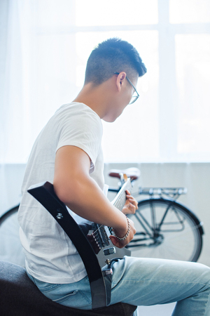 side view of asian man playing unplugged electric guitar at home Stock Photo - 110897286