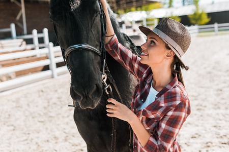 attractive female equestrian in checkered shirt and hat fixing horse halter at ranch Reklamní fotografie