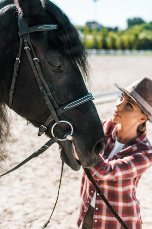 beautiful female equestrian in checkered shirt and hat fixing horse halter at ranch