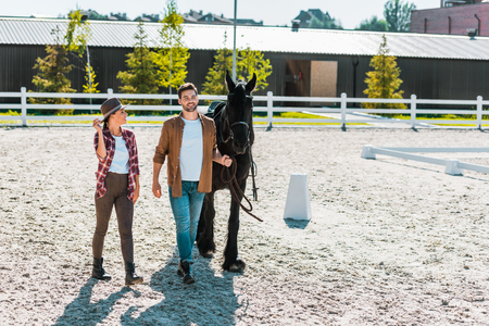 smiling cowboy and cowgirl in casual clothes walking with horse at ranch