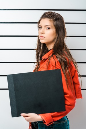 arrested young woman posing with empty prison board in front of police line up