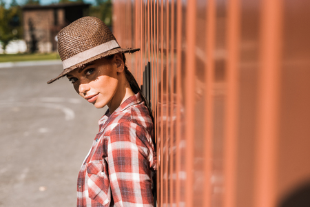 attractive cowgirl in checkered shirt and hat leaning on brown wall at ranch and looking at camera Stok Fotoğraf