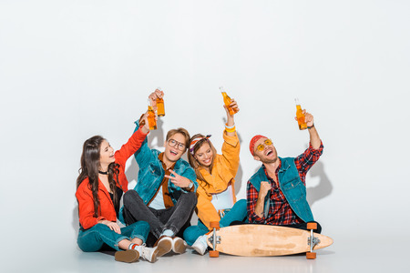 cheerful stylish hipsters sitting with skateboard and holding beer bottles