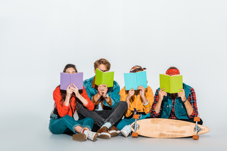 young students sitting with skateboard and holding books together