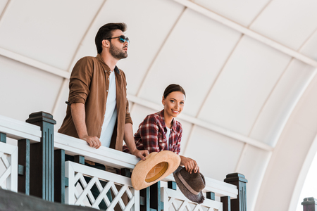 man and woman leaning on tribune railing and holding hats at ranch stadium