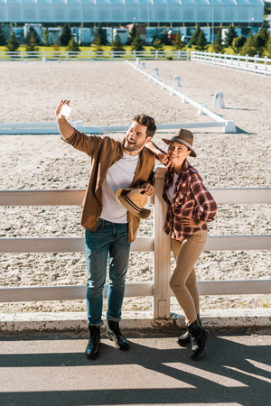 smiling stylish cowboy and cowgirl in casual clothes taking selfie with smartphone at ranch 写真素材