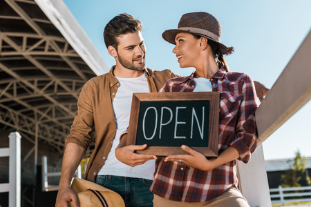 stylish cowboy and cowgirl in casual clothes holding open sign at ranch and looking at each other Stok Fotoğraf