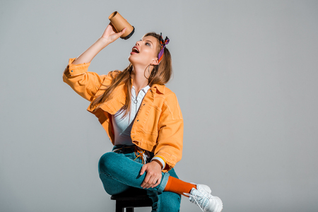 attractive stylish girl drinking coffee to go isolated on grey