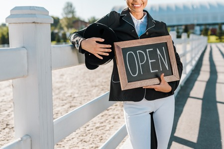 cropped image of smiling equestrian leaning on fence and holding open sign at horse club Stock Photo