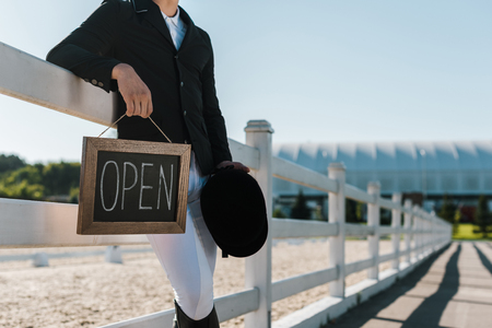 cropped image of male equestrian leaning on fence and holding open sign at ranch