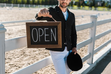 cropped image of male equestrian leaning on fence and showing open sign at horse club