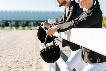 cropped image of smiling equestrians in professional apparel leaning on fence and holding riding helmets at ranch