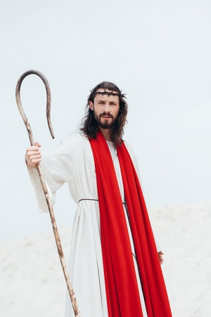 Jesus with long hair standing with wooden staff in desert