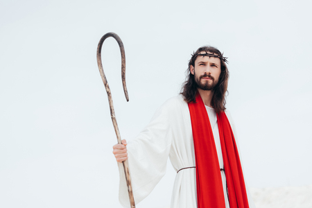 low angle view of Jesus in robe, red sash and crown of thorns standing with wooden staff in desert