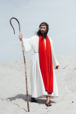 Jesus in robe, red sash and crown of thorns standing with wooden staff in desert and looking away