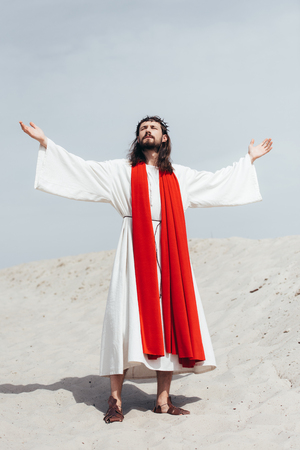 Jesus in robe, red sash and crown of thorns standing with raised hands and talking with god in desert