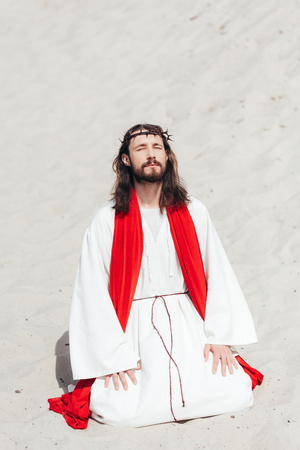 Jesus in robe, red sash and crown of thorns standing on knees with closed eyes and praying in desert