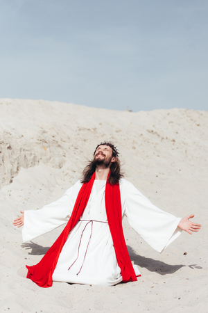 happy Jesus in robe, red sash and crown of thorns standing on knees with open arms in desert