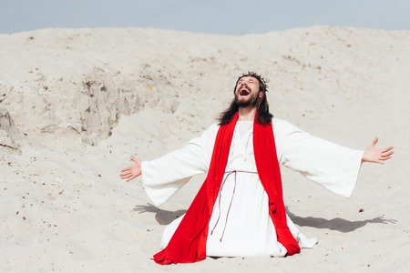 laughing Jesus in robe, red sash and crown of thorns standing on knees with open arms in desert
