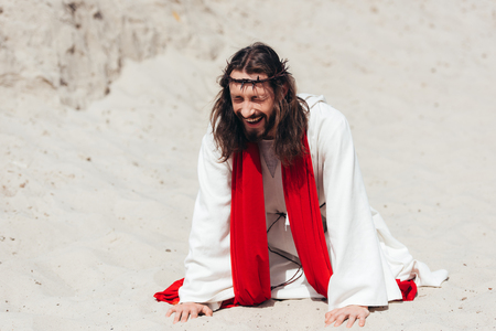 laughing Jesus in robe, red sash and crown of thorns standing on knees and touching sand with hands in desert