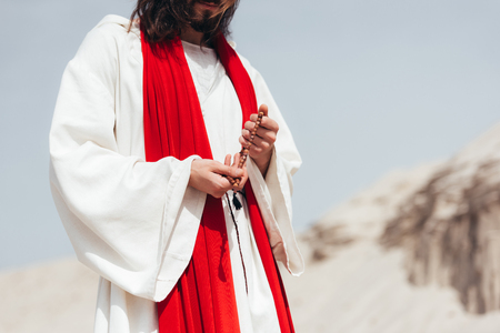 cropped image Jesus holding wooden rosary and praying in desert