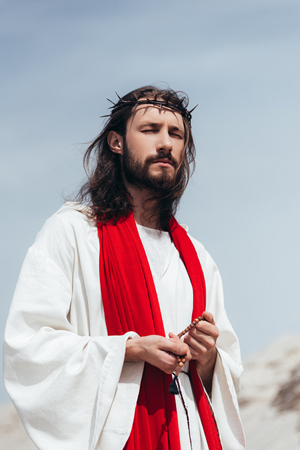 Jesus in robe, red sash and crown of thorns holding rosary and praying with closed eyes in desert Stock Photo