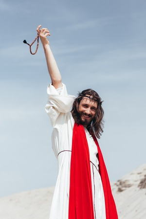 happy Jesus in robe, red sash and crown of thorns holding rosary in raised hand in desert Stock Photo