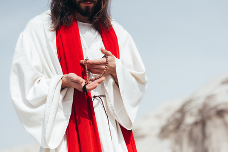 cropped image Jesus with long hair in robe and red sash holding wooden rosary in desert