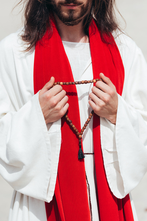 cropped image Jesus in robe and red sash holding wooden rosary in desert