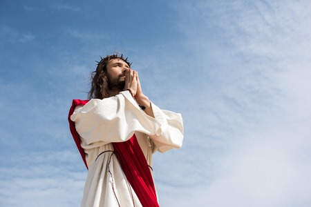 low angle view of Jesus praying against blue sky Stock Photo
