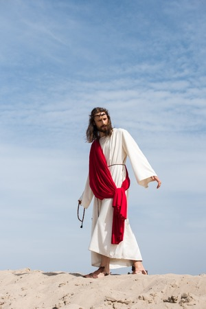 Jesus in robe, red sash and crown of thorns holding rosary and walking on sandy hill in desert