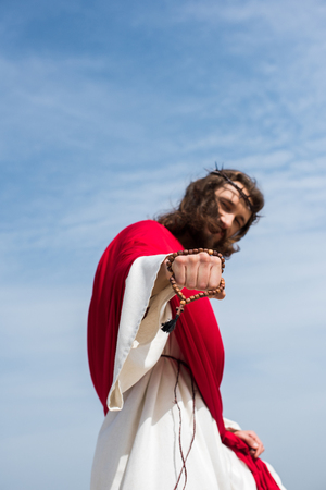 low angle view of Jesus in robe, red sash and crown of thorns showing fist with rosary against blue sky Stock Photo