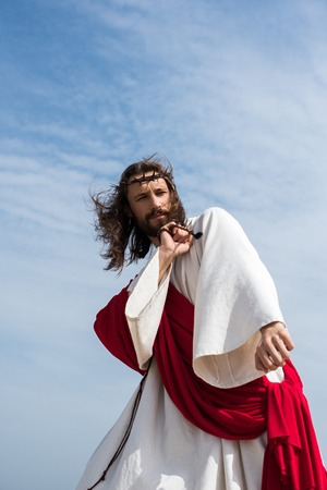 low angle view of Jesus in robe, red sash and crown of thorns having fun and dancing with rosary against blue sky