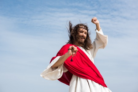 low angle view of Jesus in robe, red sash and crown of thorns having fun and jumping with rosary against blue sky