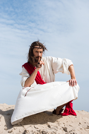 Jesus in robe, red sash and crown of thorns holding rosary and showing silence sign in desert