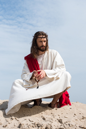 Jesus in robe, red sash and crown of thorns praying with rosary and squatting on sandy hill in desert