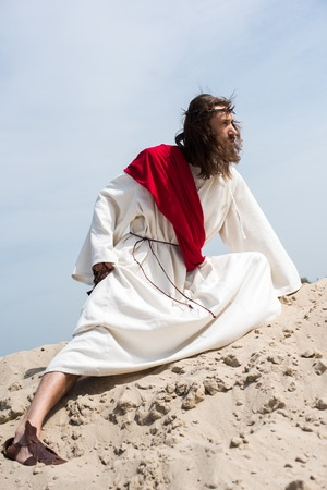side view of Jesus in robe, red sash and crown of thorns holding rosary and squatting on sandy hill in desert Stock Photo