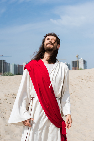 Jesus in robe, red sash and crown of thorns standing on sand with closed eyes, buildings on background
