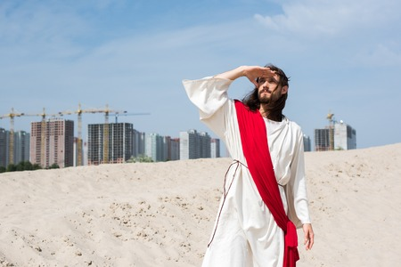 Jesus in robe, red sash and crown of thorns standing on sand and looking up with buildings on background Banque d'images - 109885412