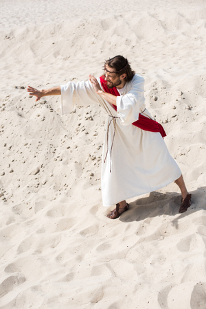 high angle view of Jesus in robe, red sash and crown of thorns standing on sand and gesturing in desert
